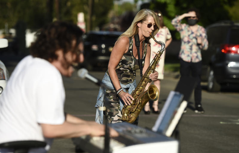 In this May 9, 2020 photo, musician Adam Chester, left, is joined by saxophonist Katja Rieckermann during his weekly neighborhood concert in the Sherman Oaks section of Los Angeles. Normally, Chester is a surrogate Elton John, who sings and plays the rock superstar's parts at rehearsals. With that work on hold, Chester has been giving concerts to his neighbors from a safe social distance in front of his house. Rieckermann is the saxophonist in singer Rod Stewart's band. (AP Photo/Chris Pizzello)