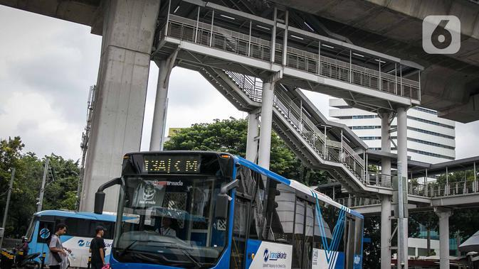 Bus Transjakarta melintas di bawah halte Transjakarta CSW di Jalan Sisingamangaraja, Jakarta, Rabu (15/1/2020). Untuk mencapai halte CSW yang setara dengan bangunan bertingkat 7 lantai tersebut harus melalui 117 anak tangga dengan ketinggian 20 meter. (Liputan6.com/Faizal Fanani)