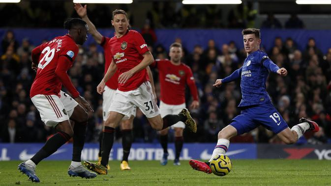 Gelandang Chelsea, Mason Mount berusaha menembak bola dari kawalan para pemain Manchester United pada pertandingan lanjutan Liga Inggris di Stamford Bridge, London (18/2/2020). MU menang 2-0 atas Chelsea. (AFP Photo/Adrian Dennis)