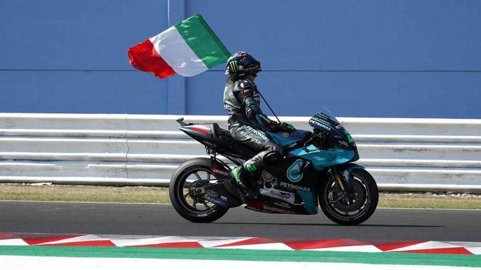 Pembalap Petronas Yamaha, Franco Morbidelli, melakukan selebrasi dengan mengibarkan bendera Italia usai menjuarai MotoGP San Marino di Sirkuit Misano, Minggu (13/9/2020). Morbidelli menjadi yang tercepat dengan catatan waktu 42 menit 02,272 detik. (AP/Antonio Calanni)