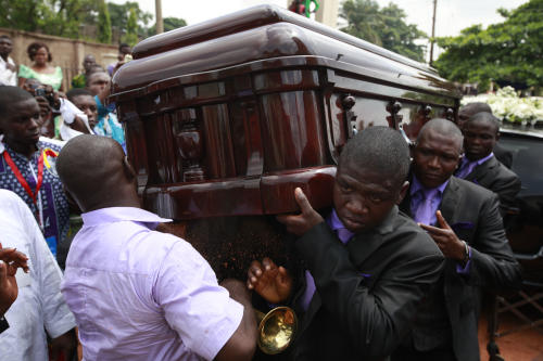 """Pallbearers carry the coffin of late author Chinua Achebe at his funeral service, held at St. Philip's Anglican Church in Ogidi, Nigeria, Thursday, May 23, 2013. Writer Chinua Achebe shunned Nigeria's corrupt politicians and twice turned down national honors, never fearing to criticizing those he felt ruined a country he once supported breaking away from. On Thursday, however, the lawmakers and the country's elite came to him. Hundreds attended Achebe's funeral among the rolling hills of his eastern Nigeria home, a service that saw even President Goodluck Jonathan literally hold up the writer's books. The gold plaque on his coffin simply called him the """"eagle atop the Iroko tree"""" in his native Igbo language. (AP Photo/Sunday Alamba)"""