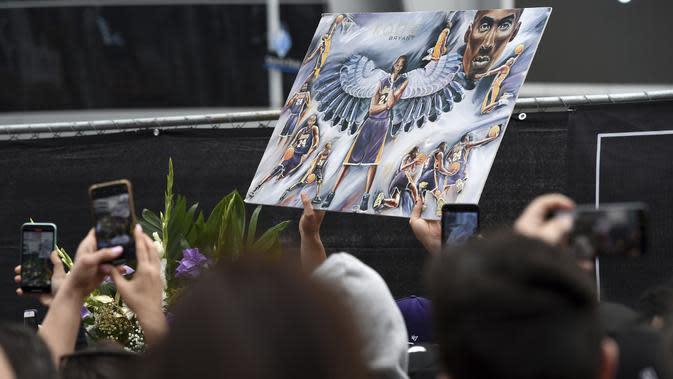 ara fans membawa foto yang menampilkan pebasket NBA Kobe Bryant di luar Staples Center di luar Staples Center, Los Angeles (26/1/2020). Putri Bryant yang berusia 13 tahun, Gianna Bryant juga ikut meninggal dunia dalam insiden tersebut. (AP Photo/Chris Pizzello)
