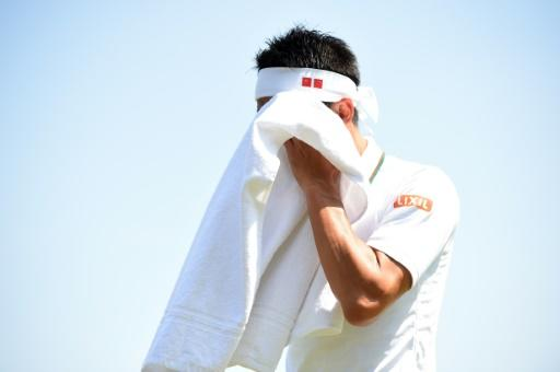 Japan's Kei Nishikori uses a towel during a break in play against Christian Harrison