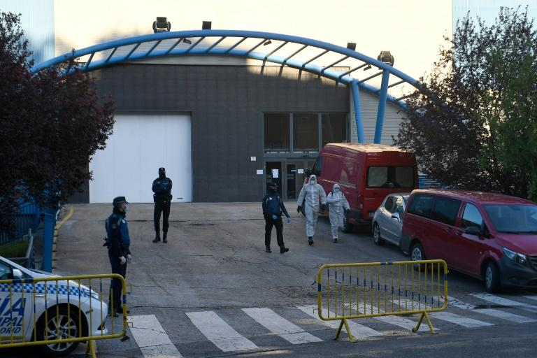 Policemen and undertakers wearing protective suits stand outside the Palacio de Hielo (Ice Palace) in Madrid s