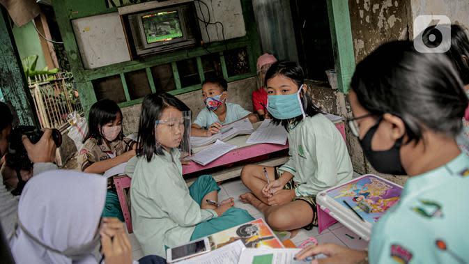 Sejumlah murid SD mengikuti kegiatan pembelajaran jarak jauh di sebuah pos keamanan RT 003 RW 006 Bendungan Hilir, Tanah Abang, Jakarta, Jumat (14/8/2020). Selama Covid-19, anak-anak memanfaatkan televisi yang ada untuk mengikuti pelajaran sekolah yang disiarkan TVRI. (Liputan6.com/Faizal Fanani)