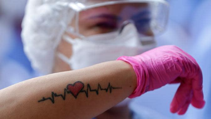 Seorang pekerja medis menunjukkan tatonya saat merayakan tiga pasien yang terakhir meninggalkan rumah sakit lapangan di Stadion Nasional Mane Garrincha di Brasilia, Brasil, Kamis (15/10/2020). Mereka berkumpul saat pasien COVID-19 terakhir pulang setelah dinyatakan sembuh. (AP Photo/Eraldo Peres)