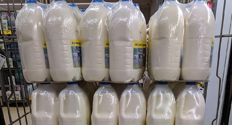 Photo of Woolworths milk wrapped in heat shrink wrap inside Melbourne supermarket.