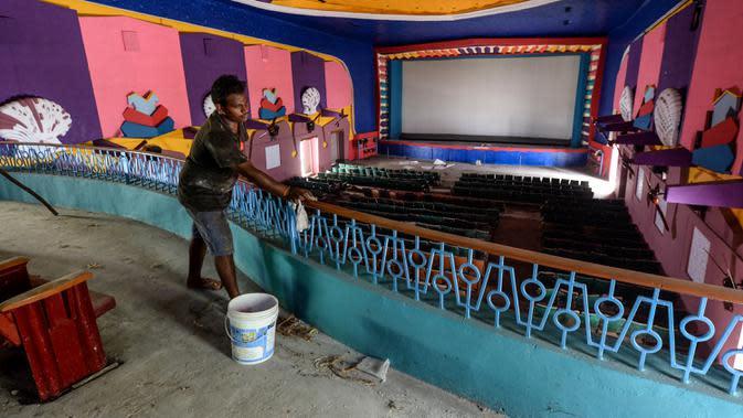 Pekerja membersihkan ruang bioskop sebagai persiapan kemungkinan pembukaan kembali setelah pemerintah melonggarkan pembatasan Covid-19, di Chennai, Sabtu (3/10/2020). Jumlah kematian di India akibat virus corona meningkat melewati 100.000 pada Sabtu, 3 Oktober 2020. (Arun SANKAR/AFP)