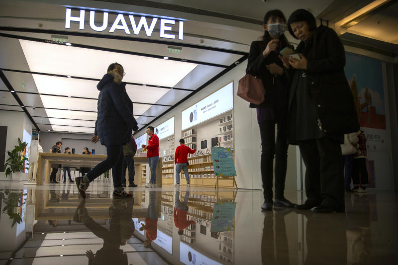 In this Nov. 20, 2019, photo, people stand outside of a Huawei store at a shopping mall in Beijing. The founder of Huawei says the Chinese tech giant is moving its U.S. research center to Canada due to American restrictions on its activities. (AP Photo/Mark Schiefelbein)