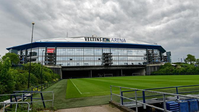 Hujan mengguyur stadion Veltins Arena markas FC Schalke 04 di Gelsenkirchen, Jerman, Rabu, (29/4/2020). Meski ada larangan pertemuan besar hingga Agustus untuk melawan pandemi Covid-19, para pejabat sepakbola berharap untuk memulai kembali liga tanpa penonton di bulan Mei. (AP/Martin Meissner)