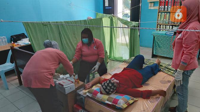 Nur yang semula tegang justru tidak merasakan sakit apa pun saat alat kontrasepsi susuk mulai dimasukkan ke dalam lengannya. Pemasangan ini dikerjakan oleh seorang bidan profesional (Foto: Aditya Eka Prawira/Liputan6.com)