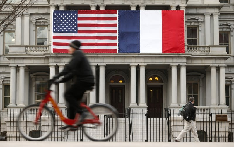 U.S. and French flags fly next to the White House to honor French President Hollande in Washington