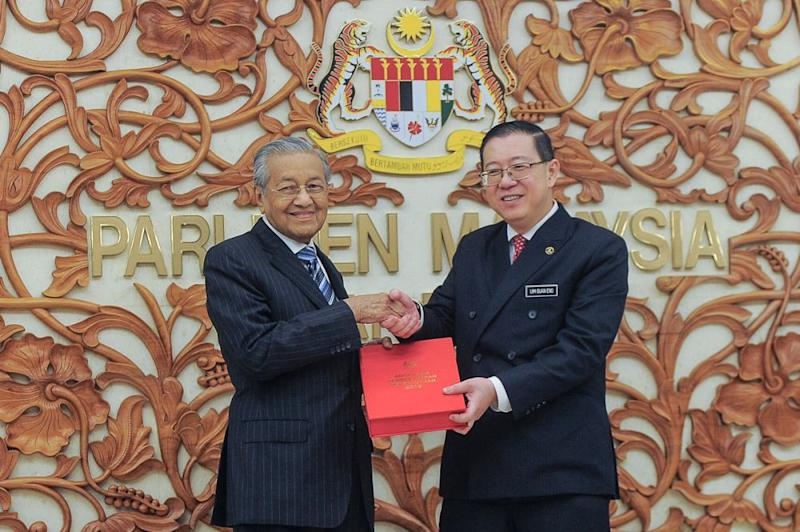 Finance Minister Lim Guan Eng and Prime Minister Tun Dr Mahathir Mohamad pose with a copy of the Budget 2019 report in Parliament November 2, 2018. — Picture by Shafwan Zaidon