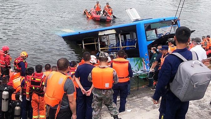Tim penyelamat berkumpul di lokasi sebuah bus yang jatuh ke danau di Anshun, China, Selasa (7/7/2020). Sedikitnya 21 orang tewas usai bus yang membawa siswa untuk mengikuti ujian masuk perguruan tinggi (gaokao) itu menabrak pagar pembatas lalu tercebur ke danau (Long Rui/Xinhua via AP)