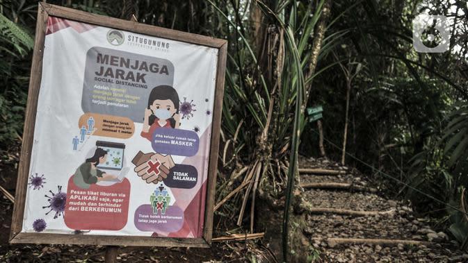 Poster imbauan protokol kesehatan Covid-19 terpasang di salah satu jalur menuju Jembatan Gantung Situ Gunung, Sukabumi, Jawa Barat, Minggu (20/9/2020). (merdeka.com/Iqbal S. Nugroho)