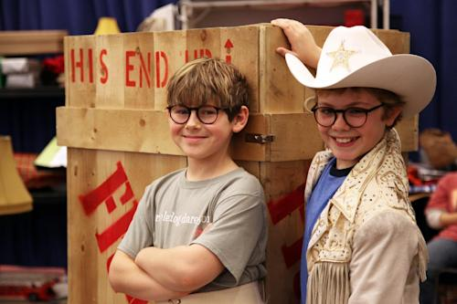 "In this Oct. 26, 2012, photo, Johnny Rabe, left, and Joe West pose in front of one of the props from ""A Christmas Story, the Musical"" in New York. Both 12-year-old boys are making their Broadway debuts playing Ralphie in the stage adaptation of the cult 1983 film. (AP Photo/Mark Kennedy)"