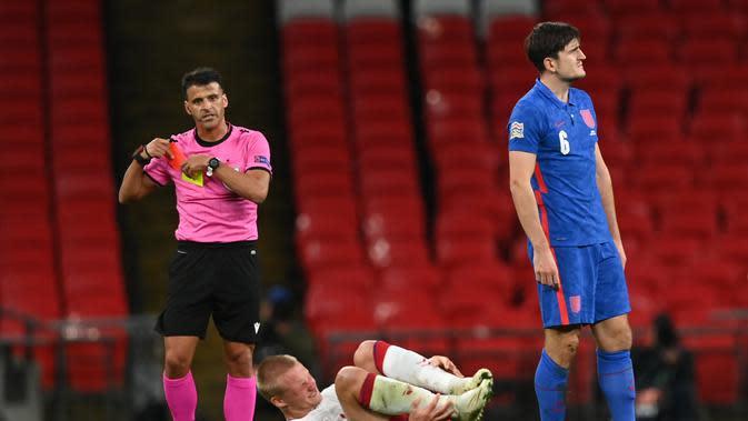 Wasit Jesús Gil Manzano (Kiri) menarik kartu merah untuk bek Inggris, Harry Maguire setelah menjegal penyerang Denmark, Kasper Dolberg dalam lanjutan pertandingan UEFA Nations League grup A2 di stadion Wembley di London (14/10/2020). Inggris takluk atas Denmark 0-1. (AFP/Pool/Daniel Leal-Olivas)