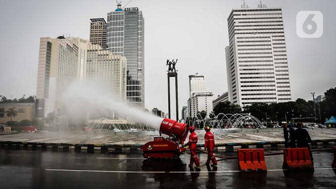 Petugas pemadam kebakaran menyemprotkan cairan disinfektan menggunakan robot LUF 60 di kawasan Bundaran HI, Jakarta, Minggu (22/3/2020). Pemprov DKI Jakarta melakukan penyemprotan fasilitas umum untuk mencegah penyebaran virus corona COVID-19. (Liputan6.com/Faizal Fanani)