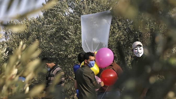 Sejumlah pria Palestina menyiapkan balon dengan alat peledak yang akan diterbangkan ke arah Israel di dekat kamp pengungsi al-Bureij, sepanjang perbatasan Israel- Jalur Gaza (12/8/2020). (AFP Photo/Mohammed Abed)