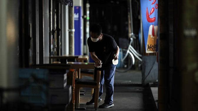 Seorang karyawan restoran yang mengenakan masker untuk membantu mencegah penyebaran virus corona membersihkan meja sebelum dibuka di Tokyo, Kamis (10/9/2020). Ibu kota Jepang itu mengonfirmasi lebih dari 270 kasus virus corona pada Kamis. (AP Photo / Eugene Hoshiko)