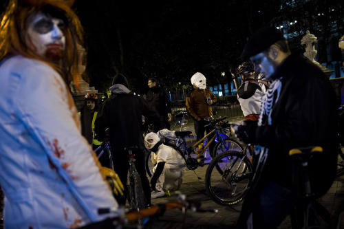 """People, most of them dressed with Halloween costumes, take part in the flash mob """"Halloween bike ride"""" before touring around the city in Madrid, Tuesday, Oct. 31, 2012. (AP Photo/Daniel Ochoa de Olza)"""
