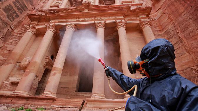 Petugas menyemprotkan cairan disinfektan di kota arkeologi Petra, Yordania, 17 Maret 2020. Berdasarkan data terbaru Universitas Johns Hopkins pada 21 Maret 2020, jumlah kasus virus corona COVID-19 di Yordania mencapai 85 orang. (Photo by Khalil MAZRAAWI/AFP)