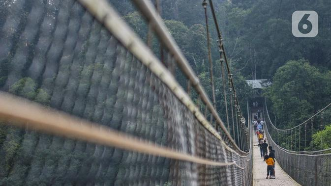 Pengunjung melintasi Jembatan Gantung Situ Gunung di Sukabumi, Minggu (20/9/2020). Dari rata-rata 2.500 pengunjung tiap harinya kini hanya di bawah 1.000 pelancong per hari akibat merebaknya pandemi Covid-19 serta adanya penerapan PSBB. (merdeka.com/Iqbal S. Nugroho)