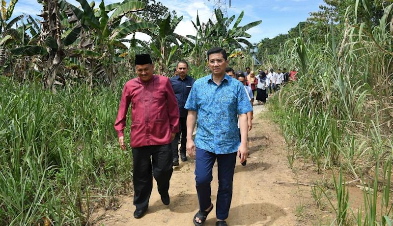 PKR deputy president and Minister of Economic Affairs Datuk Seri Mohamed Azmin Ali, accompanied by Assemblyman Datuk Mohd Arifin Arif (left) walking to a get-together with locals in Kampung Baitam Baru, Kimanis, Sabah, January 17, 2020. — Bernama pic