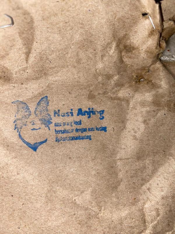 Bungkus nasi anjing yang menghebohkan warga Jakarta Utara. Terdapat logo kepala anjing dengan tulisan: nasi anjing, nasi orang kecil, bersahabat dengan kucing #Jakartatahanbanting. (Ist)
