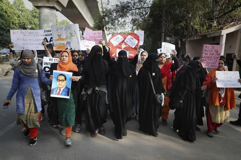 A students holds a photograph of Bhima Rao Ambedkar as Indian students of the Jamia Millia Islamia University march during a protest, in New Delhi, India, Wednesday, Dec. 18, 2019. (AP Photo/Altaf Qadri)