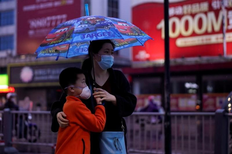 People wearing face masks walk in Jingzhou