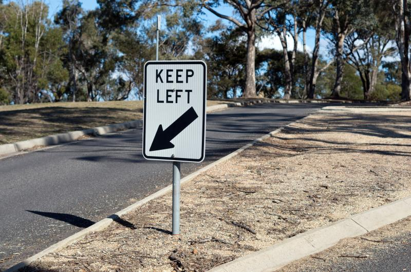 """Photo of a """"keep left"""" sign on the road."""