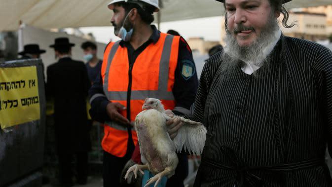 Seorang pria Yahudi ultra-Ortodoks membawa seekor ayam untuk diayunkan di atas kepala keluarganya sebagai bagian dari ritual Kaparot di Yerusalem, Rabu (23/9/2020). Ayam ini kemudian akan disembelih menjadi pengganti seseorang tersebut sebagai penebusan untuk dosa-dosanya. (AP Photo/Maya Alleruzzo)
