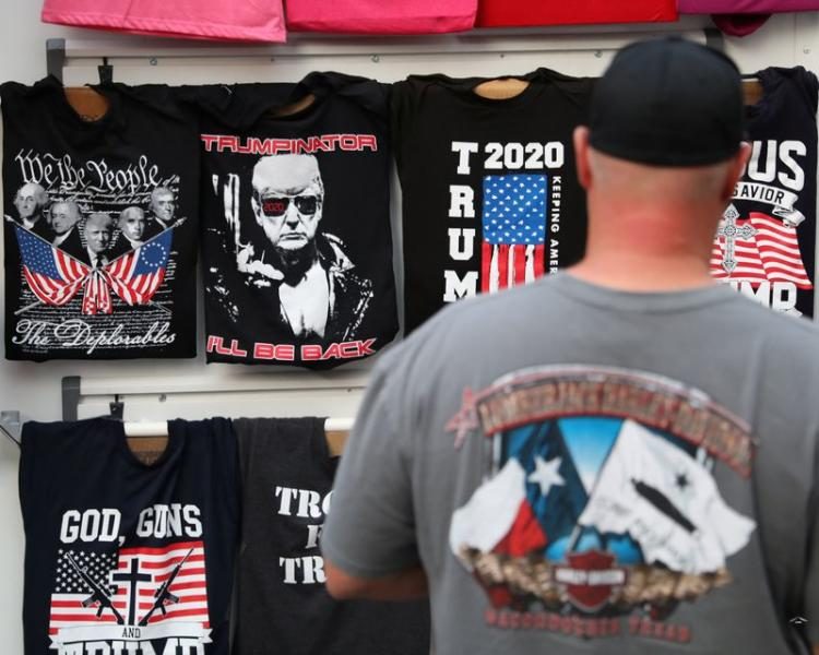 A man looks at T-shirts a day before U.S. President Donald Trump holds a rally in Tulsa