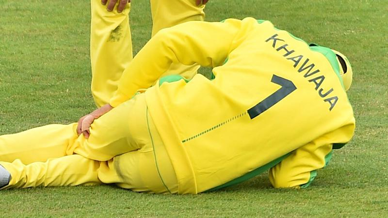 Usman Khawaja lies on the ground after being hit by the ball. (Photo by GLYN KIRK/AFP/Getty Images)