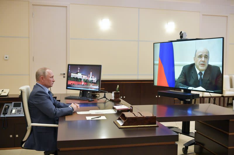 Russian President VladimirPutin listens to Prime Minister Mikhail Mishustin during their meeting via a video link outside Moscow