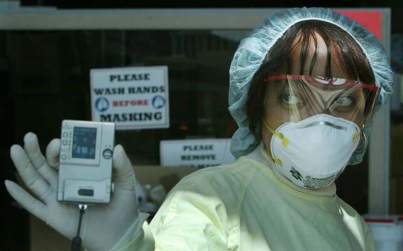 FILE PHOTO: NURSE WEARING MASK SHOWS PHOTO TO MEDIA.