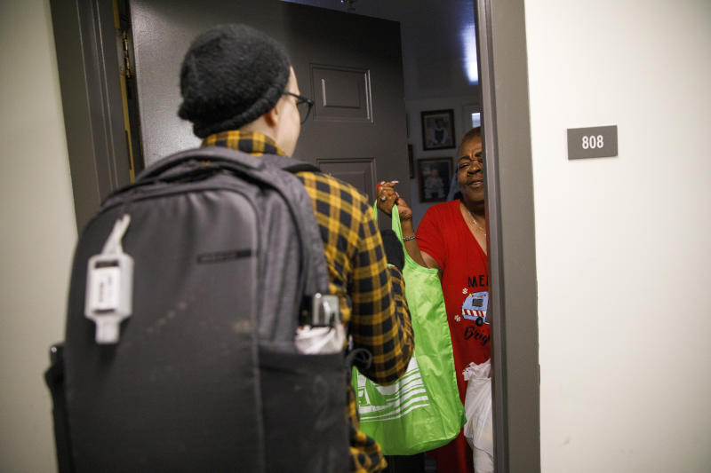 """Denise Edmondson, 66, of Washington, right, greets Noel Schroeder, with the nonprofit organization """"We Are Family DC,"""" as she delivered groceries to Edmondson's apartment door, Saturday, March 21, 2020, in Washington. Seniors are being encouraged to stay in their homes due to the risk of the COVID-19 coronavirus. (AP Photo/Jacquelyn Martin)"""