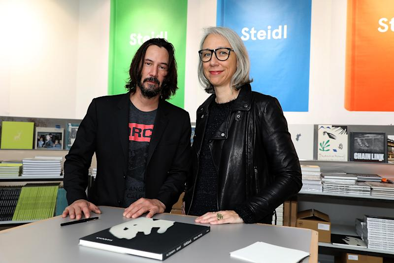 A photo of Alexandra Grant and Keanu Reeves posing with their book, Ode to happiness, in 2017 in Paris