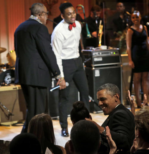 "President Barack Obama, center seated, looks over toward his daughter Sasha, as singers Sam Moore, left, and Joshua Ledet, right, perform on stage during the ""In Performance at the White House"" in the East Room of the White House in Washington, Tuesday, April 9, 2013, a program for a celebration of Memphis Soul Music. (AP Photo/Pablo Martinez Monsivais)"