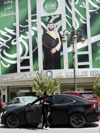 Majdoleen Mohammed Alateeq, a newly-licensed Saudi driver, gets out of her car next to a poster of the Crown Prince Mohammed bin Salman in the Saudi capital Riyadh