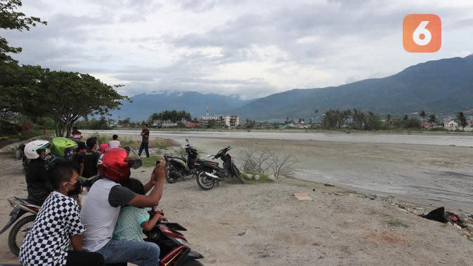 Puluhan warga yang telah berkumpul di tepi Muara Sungai Palu sejak pukul 17.00 Wita untuk menyaksikan buaya-buaya yang muncul di muara yang sedang surut, Rabu (20/5/2020). (Foto: Liputan6.com/ Heri Susanto).