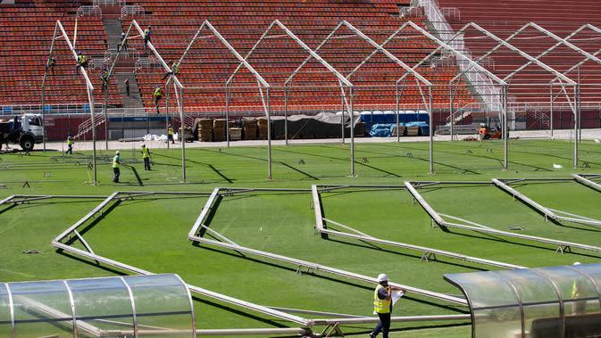 Pekerja membangun rumah sakit darurat bagi pasien terinfeksi Covid-19 di lapangan stadion Pacaembu, di Sao Paulo, Senin (23/3/2020). Sejumlah klub sepakbola papan atas Brasil meminjamkan stadion ke otoritas setempat untuk diubah menjadi rumah sakit atau klinik darurat virus corona. (AP/Andre Penner)