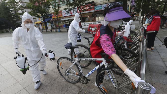 Pekerja dan sukarelawan mendisinfeksi jalan di Goyang, Korea Selatan, Selasa (25/8/2020). Korea Selatan menutup sekolah dan beralih kembali ke pembelajaran jarak jauh setelah memasuki hari ke-12 peningkatan berturut-turut dalam kasus COVID-19. (AP Photo/Ahn Young-joon)
