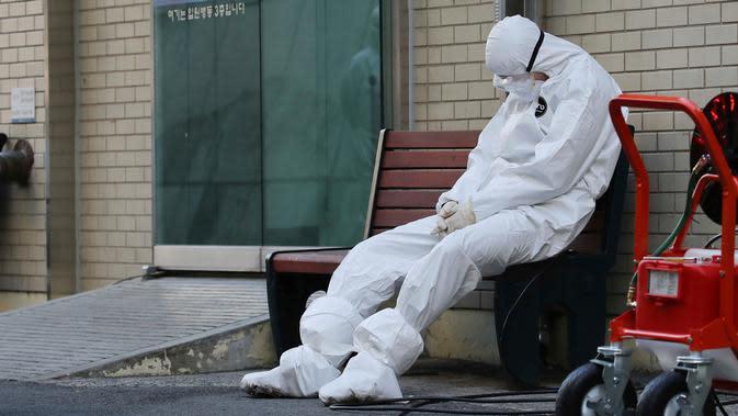 Petugas medis beristirahat saat menunggu pasien virus corona (COVID-19) di luar sebuah rumah sakit di Daegu, Korea Selatan, Minggu (23/2/2020). Daegu menjadi pusat penyebaran virus corona di Korea Selatan. (Im Hwa-young/Yonhap via AP)