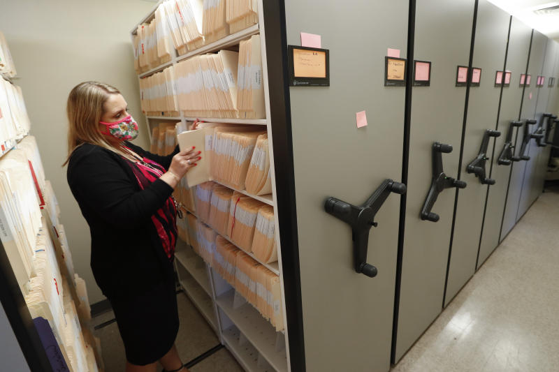 Jennifer Gottschalk, environmental health supervisor of the Toledo-Lucas County Health Department, retrieves a file in Toledo, Ohio, on Wednesday, June 24, 2020. She says the job is wearing on her. She has worked for months with hardly a day off. So many lab reports on COVID-19 cases came in that the office fax machine broke. And she fields countless angry phone calls amid community backlash over coronavirus restrictions. (AP Photo/Paul Sancya)