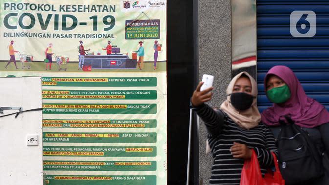 Warga berfoto di samping spanduk sosialisasi COVID-19 di Pasar Blok A Tanah Abang, Jakarta, Selasa (1/9/2020). Guna meningkatkan kewaspadaan masyarakat, muspida kecamatan Tanah Abang memajang peti mati dilengkapi data jumlah korban COVID-19 di wilayah tersebut. (Liputan6.comHelmi Fithriansyah)