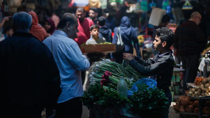 Warga Palestina berbelanja untuk persiapan menjelang bulan suci Ramadan di pasar al-Zawiya di Kota Gaza pada 20 April 2020. Tahun ini, miliaran umat Muslim di dunia bersiap memasuki bulan suci Ramadan di tengah situasi pandemi Covid-19. (MAHMUD HAMS / AFP)