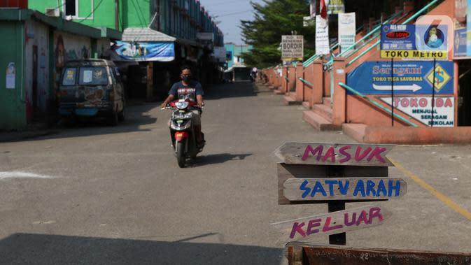 Warga melintasi pintu masuk kawasan Pasar Cileungsi yang ditutup sementara, Kabupaten Bogor, Selasa (2/6/2020). Penutupan sementara kegiatan jual beli di Pasar Cileungsi terkait adanya tujuh pedagang yang positif terinfeksi virus COVID-19. (Liputan6.com/Helmi Fithriansyah)