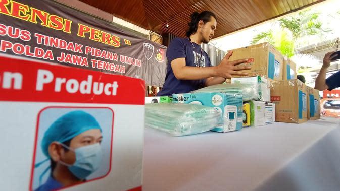 Petugas merapikan masker saat melakukan gelar atas penangkapan penimbun masker dan hand sanitizer di Polda Jateng, Semarang, Selasa (4/3/2020). Dua orang ditangkap berinisial AK (45) warga Kanalsari Barat, Semarang Timur dan M (24) warga Kapas timur VIII, Genuk Semarang. (Liputan6.com/Gholib)